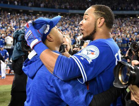 Toronto Blue Jays designated hitter Edwin Encarnacion (10) celebrates with Toronto Blue Jays starting pitcher Marcus Stroman (6) after beating the Baltimore Orioles in the American League wild card playoff baseball game at Rogers Centre. Mandatory Credit: Nick Turchiaro-USA TODAY Sports