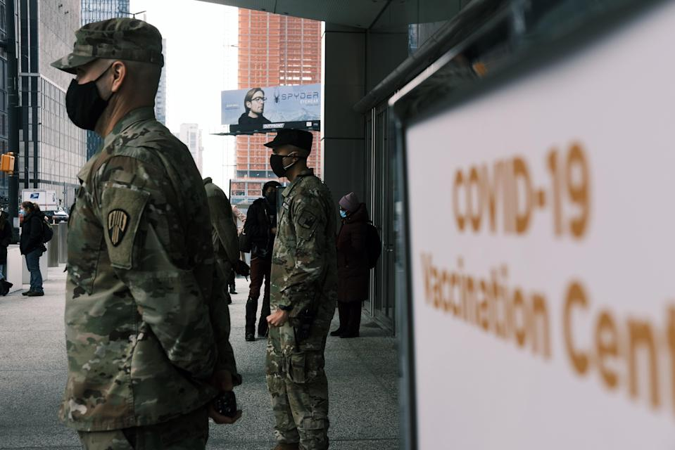<p>Members of the National Guard assist people at Manhattan's Javits Center which recently opened as a Covid vaccination site</p> (Getty Images)