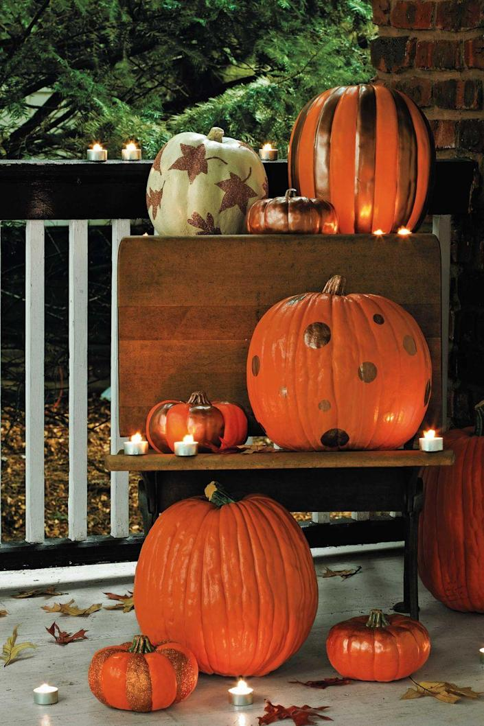 """<p>Gild your gourds with metallic paint. Follow the natural ridges of the pumpkin for a fun stripe, or use stencils to paint other patterns onto the surface. The effect is especially pretty when you mix in different-colored pumpkins. </p><p><a class=""""link rapid-noclick-resp"""" href=""""https://www.amazon.com/Art-Supply-Metallic-Acrylic-Bottles/dp/B07GYYG35L/?tag=syn-yahoo-20&ascsubtag=%5Bartid%7C10070.g.1902%5Bsrc%7Cyahoo-us"""" rel=""""nofollow noopener"""" target=""""_blank"""" data-ylk=""""slk:SHOP METALLIC PAINTS"""">SHOP METALLIC PAINTS</a> </p>"""