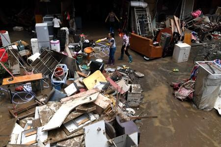 Residents clean up their belongings after their houses were hit by flood following heavy rainfall in Sanming