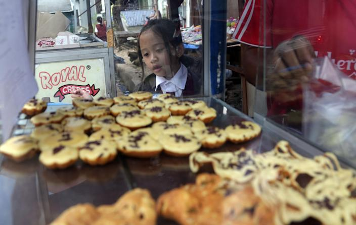 A public elementary school girl buys a pancake for her lunch on the street in Jakarta, Indonesia, Tuesday, May 6, 2014. In Indonesia, not every student can bring a lunch box to school. Public school students buy their lunch at school cafeterias or food stalls on the nearby streets. The price for one pancake is about one U.S. cent. (AP Photo/Achmad Ibrahim)