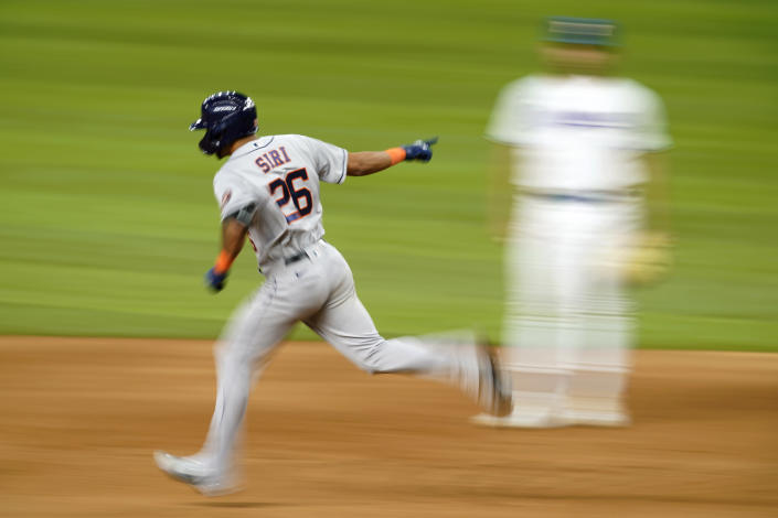 Houston Astros' Jose Siri (26) celebrates his solo home run as he rounds the bases past Texas Rangers first baseman Nathaniel Lowe in the eighth inning of a baseball game in Arlington, Texas, Monday, Sept. 13, 2021. (AP Photo/Tony Gutierrez)