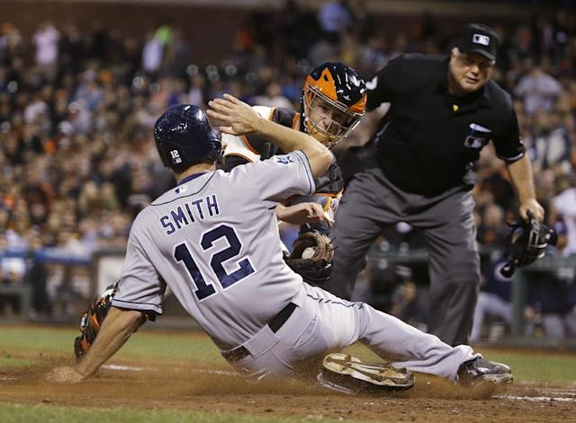 San Diego Padres' Seth Smith is tagged out at home plate by San Francisco Giants catcher Buster Posey as home plate umpire Brian O'Nora watches during the sixth inning of a baseball game Tuesday, June 24, 2014, in San Francisco. Smith tried to score from second on a single by Yasmani Grandal to center. (AP Photo/Eric Risberg)
