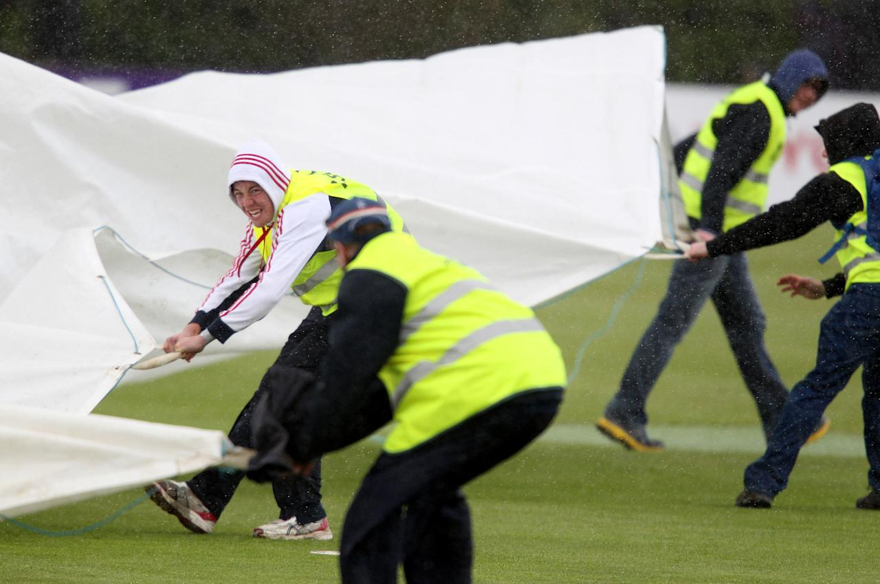 Groundstaff try to place a cover over the crease as rain delays the One Day International (ODI) cricket match between Pakistan and Ireland at Clontarf Cricket Club in Dublin on May 23, 2013.