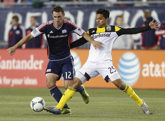 New England Revolution's Andy Dorman (12) and Columbus Crew's Jairo Arrieta (25) vie for the ball in the first half of an MLS soccer game in Foxborough, Mass., Saturday, Oct. 19, 2013. (AP Photo/Michael Dwyer)