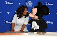 <p>Disney's rodent-in-chief smooches Oprah while her handprints are preserved. (Photo: Disney) </p>