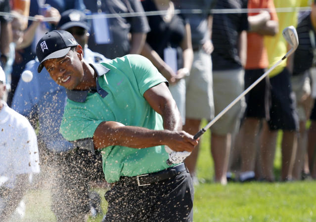 Tiger Woods hits out of the sand to the 13th green during the first round of the BMW Championship golf tournament at Conway Farms Golf Club in Lake Forest, Ill., Thursday, Sept. 12, 2013. (AP Photo/Charles Rex Arbogast)