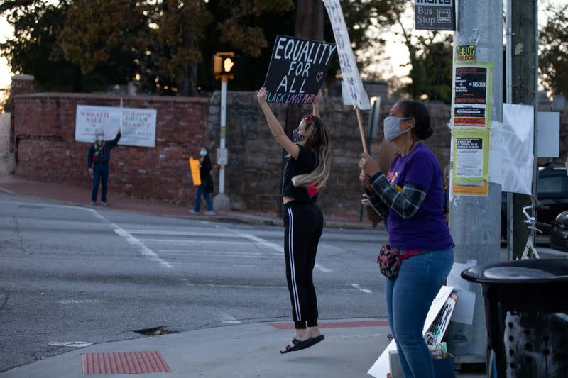 Protesters hold signs on equality as they demonstrate at an intersection near Downtown in Atlanta