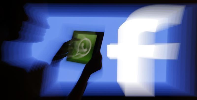 Woman holds a tablet displaying WhatsApp's logo in front of the screen with the Facebook logo in this photo illustration taken in Prague