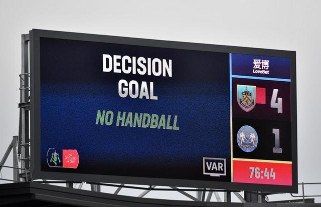 A VAR decision on handball is displayed on a screen at Peterborough