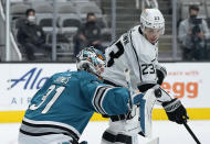 San Jose Sharks goaltender Martin Jones (31) blocks a shot as Los Angeles Kings right wing Dustin Brown (23) looks for a rebound during the second period of an NHL hockey game Saturday, April 10, 2021, in San Jose, Calif. (AP Photo/Tony Avelar)