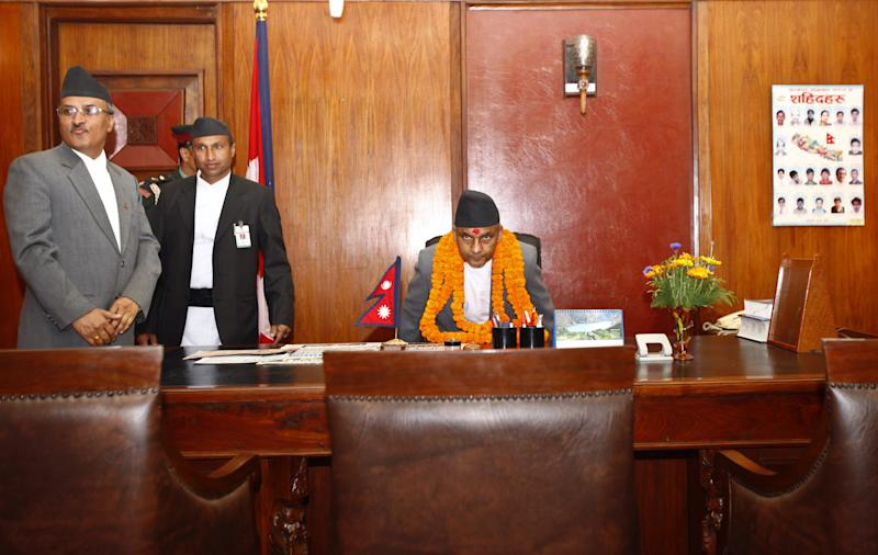 Nepal's newly-appointed Prime Minister Khilraj Regmi, center, assumes office after being sworn in in Katmandu, Nepal, Thursday, March 14, 2013. Nepal's chief judge became head of an interim government Thursday that is charged with holding elections in three months to replace the parliament whose term expired almost a year ago. (AP Photo/Niranjan Shrestha)