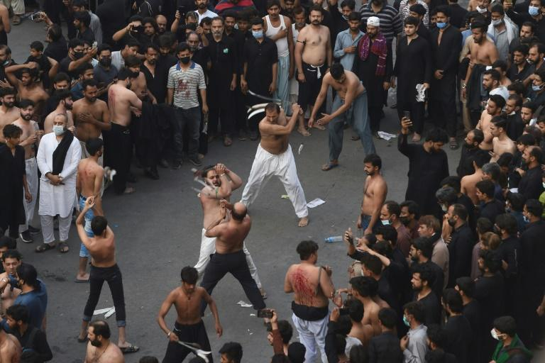 Dressed in black, devotees chanted slogans and slapped their chests in unison while others whipped themselves with blades at the Lahore procession