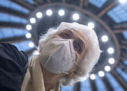 CORRECTS MONTH TO JANUARY - After receiving her vaccination against the novel coronavirus, 90-year-old Odores H. sits under the domed roof of the vaccination centre in the Festhalle in Frankfurt, Tuesday, Jan. 19, 2021. This is where thousands of people usually gather for concerts and trade fairs, and where the state of Hesse operates one of its vaccination centers. (Boris Roessler/dpa via AP)