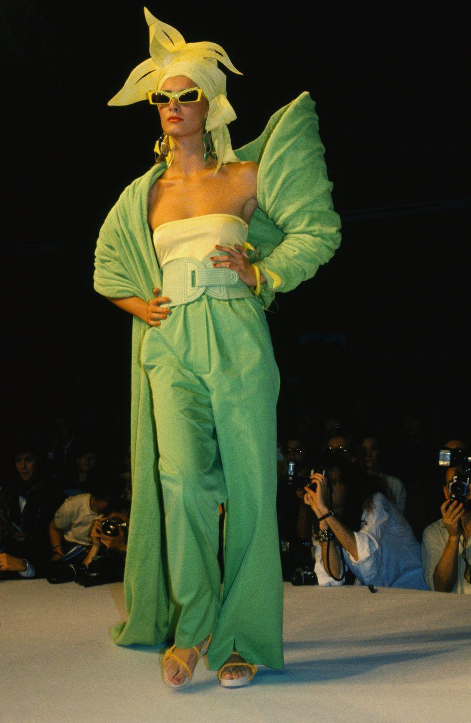 <p>A model in an all-green look and matching sunglasses walks the Claude Montana runway at Paris Fashion Week. </p>