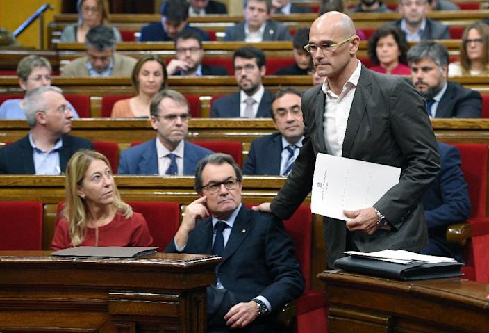 """Leader of the Catalan pro-independence coalition """"Junts pel Si"""" (""""Together for the Yes"""") Raul Romeva (R) walks past regional leader Artur Mas (C) during a session at the Catalan Parliament in Barcelona, on November 9, 2015 (AFP Photo/Lluis Gene)"""