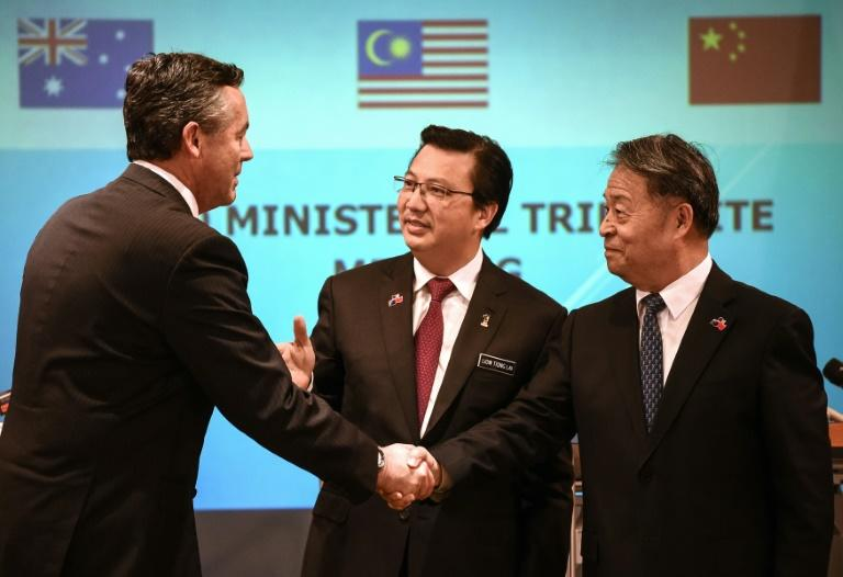 Malaysia's Transport Minister Liow Tiong Lai (C), Australia's Minister for Infrastructure and Transport Darren Chester (L) and Chinese Minister of Transport Yang Chuantang shake hands after a joint press conference in Putrajaya, in June 2016