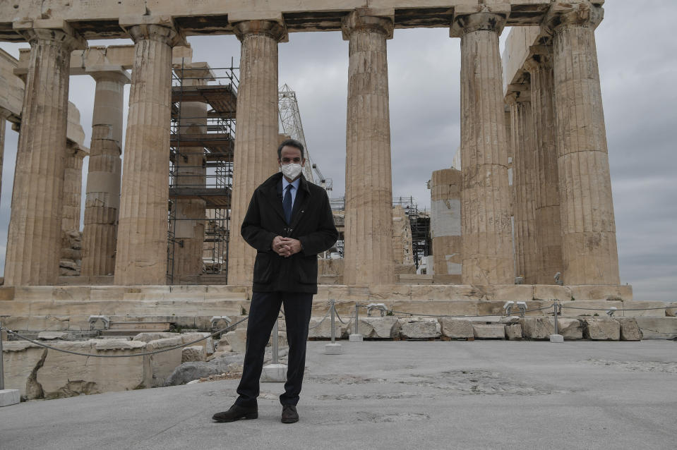 Greek Prime Minister Kyriakos Mitsotakis stands in front of the ancient Parthenon Temple at the Acropolis hill, in Athens, Thursday, Dec. 3, 2020, Acropolis became fully accessible to the disabled and those with mobility issues with a restoration of its terrain and a new elevator. Mitsotakis visited the completed works to mark the international Day for people with disabilities. (Louisa Gouliamaki/Pool via AP)