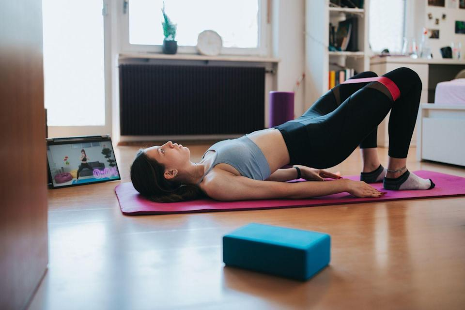 """<p><strong>Alvarez</strong> brings an extra level to the hip bridge by adding abduction. She says that this activates the outer thigh, glutes, and even the lower abdominals. Alvarez especially likes this move for mothers to help strengthen and tighten the muscles and ligaments around the hips that may have weakened after giving birth.</p><p><strong>How to:</strong> Lay on your back with your knees bent and feet on the floor. Place a <a href=""""https://www.goodhousekeeping.com/health-products/g32334989/best-resistance-bands/"""" rel=""""nofollow noopener"""" target=""""_blank"""" data-ylk=""""slk:resistance band"""" class=""""link rapid-noclick-resp"""">resistance band</a> above your knees, and space out your feet so that there is tension on the band. Keeping the band tense, squeeze your glutes and lift your hips up to a bridge. Once in the bridge push your knees out to the sides. Bring knees in and lower hips to return to the start. Aim to do this 20 times without stopping, and remember to move slowly and with control.<br></p>"""