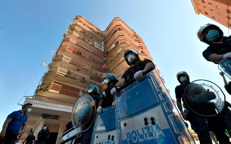 Italian riot police stand guard at the estate - ANSA