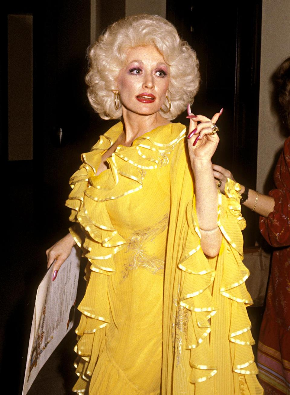 """<p>Parton's longtime costume designer, Steve Summers, describes her mid-'70s style as """"a butterfly look."""" And this bright yellow outfit from 1979 features subtle butterfly motifs throughout. </p>"""