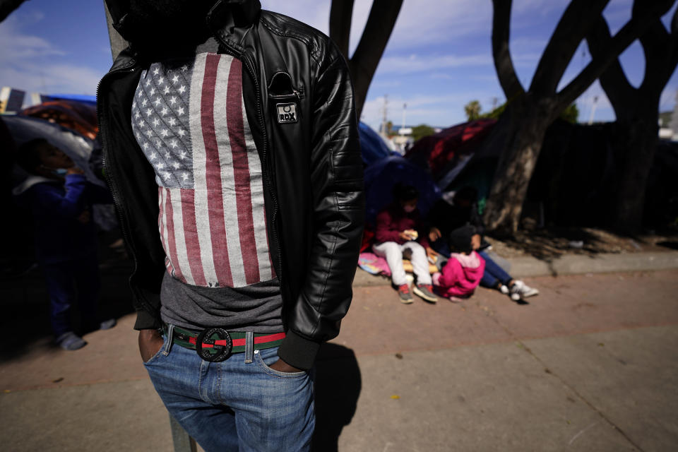 A migrant asylum seeker from Haiti waits at a makeshift camp of migrants at the border port of entry leading to the United States, Wednesday, March 17, 2021, in Tijuana, Mexico. The migrant camp shows how confusion has undercut the message from U.S. President Joe Biden that it's not the time to come to the United States. Badly misinformed, some 1,500 migrants who set up tents across the border from San Diego harbor false hope that Biden will open entry briefly and without notice. (AP Photo/Gregory Bull)