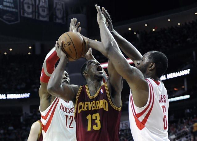 Cleveland Cavaliers' Tristan Thompson (13) is sandwiched between Houston Rockets defenders Dwight Howard (12) and Terrence Jones (6) in the first half of an NBA basketball game Saturday, Feb. 1, 2014, in Houston. (AP Photo/Pat Sullivan)