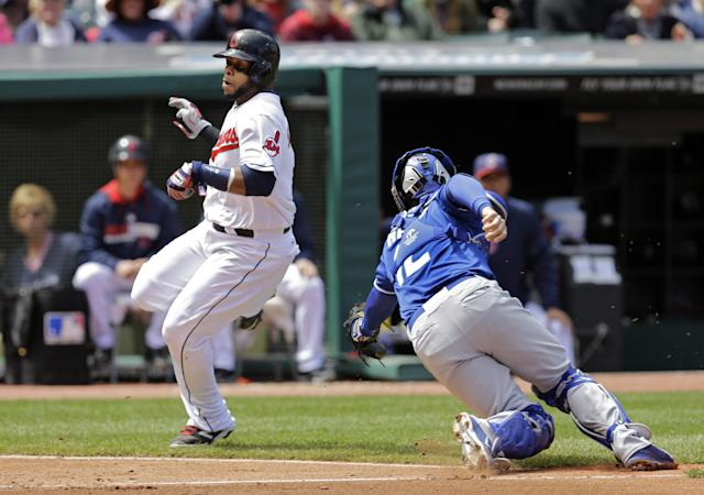 Cleveland Indians' Carlos Santana, left, avoids the tag from Kansas City Royals catcher Brett Hayes to score on a single by Michael Brantley in the fifth inning of a baseball game Thursday, April 24, 2014, in Cleveland. (AP Photo/Mark Duncan)