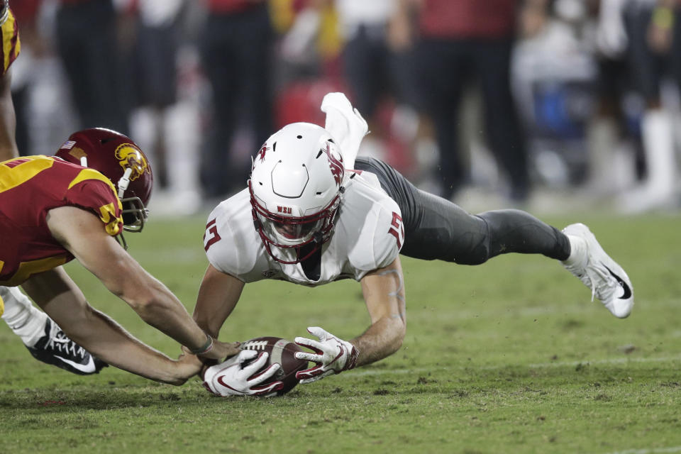 Washington State wide receiver Kyle Sweet, right, recovers his own fumble next to Southern California linebacker Isaac Franco during the first half of an NCAA college football game Friday, Sept. 21, 2018, in Los Angeles. (AP Photo/Jae C. Hong)