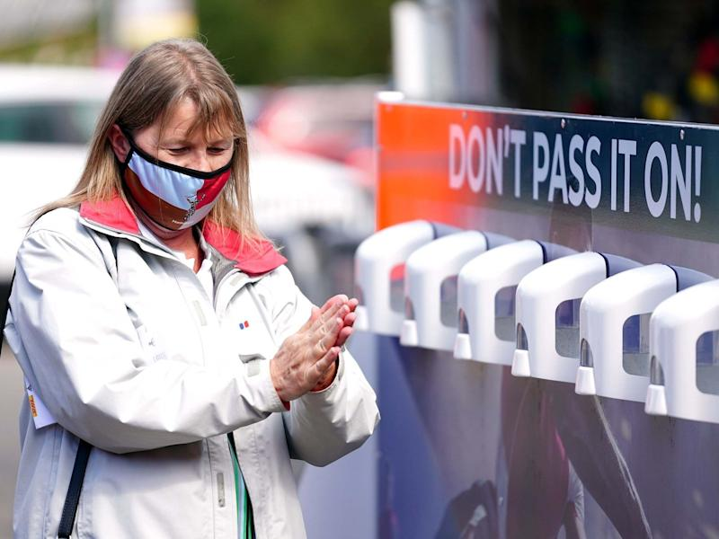 A Harlequins fan using the sanitiser provided outside the ground at Twickenham Stoop, London: PA