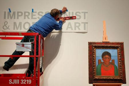 A man hangs a sign as artist Frida Kahlo's painting 'Nina Con Collar' sits on an easel at Sotheby's auction house in New York U.S., November 14, 2016. REUTERS/Shannon Stapleton