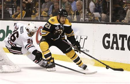 Bruins' Thornton is chased by Blackhawks Handzus during Game 3 of the NHL Stanley Cup Finals in Boston