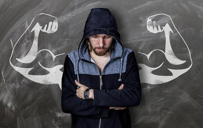 A young man in a hoodie looks pensive with his arms folded across his chest. Behind him, on a blackboard, a drawing of caricatured muscular arms lines up with his shoulders.