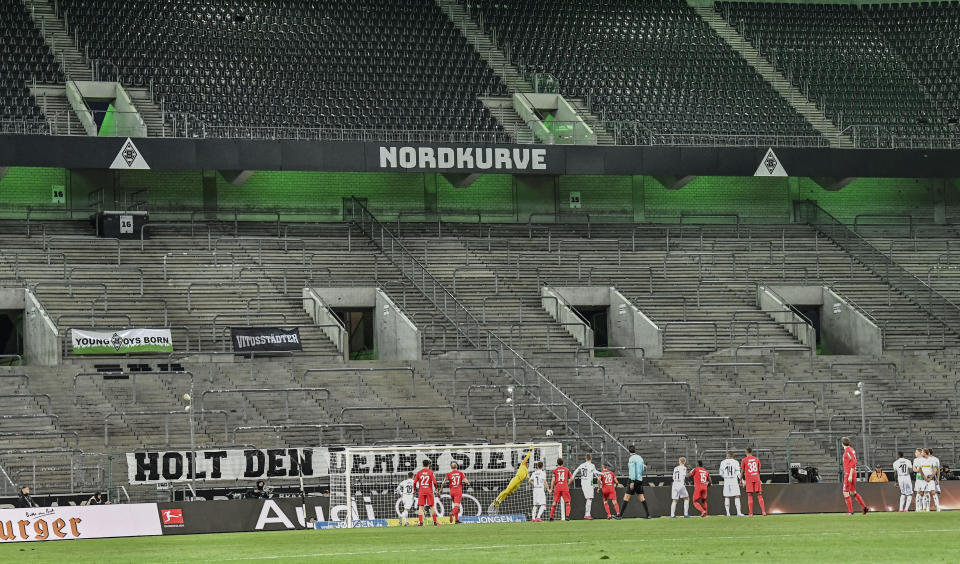 Players challenge for the ball in an empty stadium during the German Bundesliga soccer match between Borussia Moenchengladbach and 1.FC Cologne in Moenchengladbach, Germany, Wednesday, March 11, 2020. It is the first Bundesliga match played behind closed doors without spectators due to the coronavirus outbreak. For most people, the new coronavirus causes only mild or moderate symptoms, such as fever and cough. For some, especially older adults and people with existing health problems, it can cause more severe illness, including pneumonia. (AP Photo/Martin Meissner)