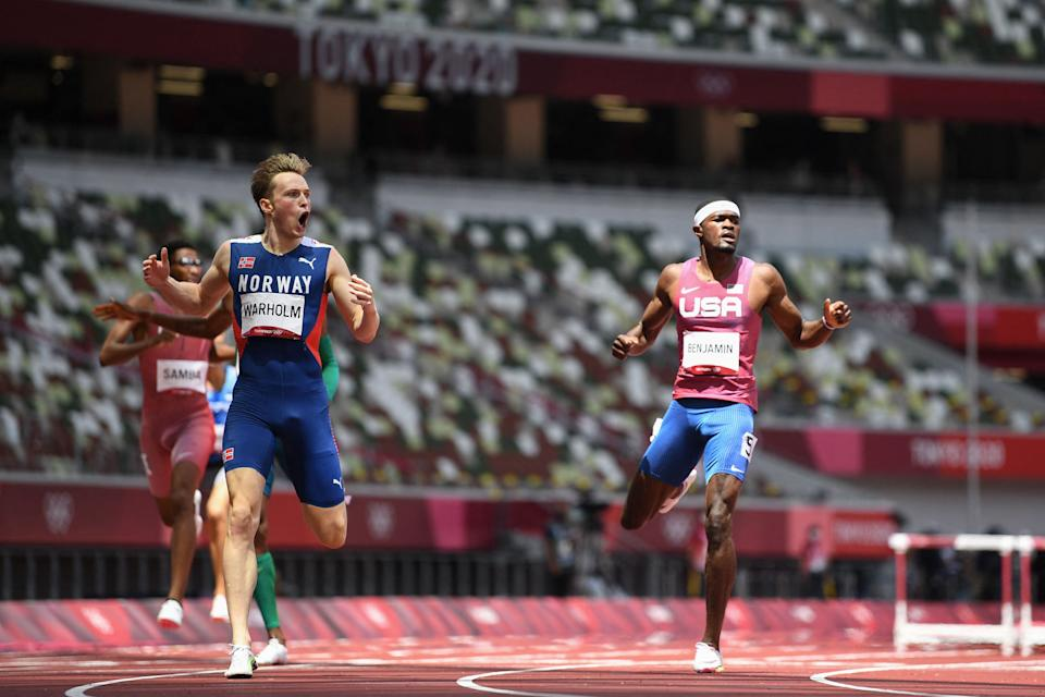 Norway's Karsten Warholm (L) reacts as he wins and breaks the world record ahead of second-placed  USA's Rai Benjamin (R) in the men's 400m hurdles final during the Tokyo 2020 Olympic Games.