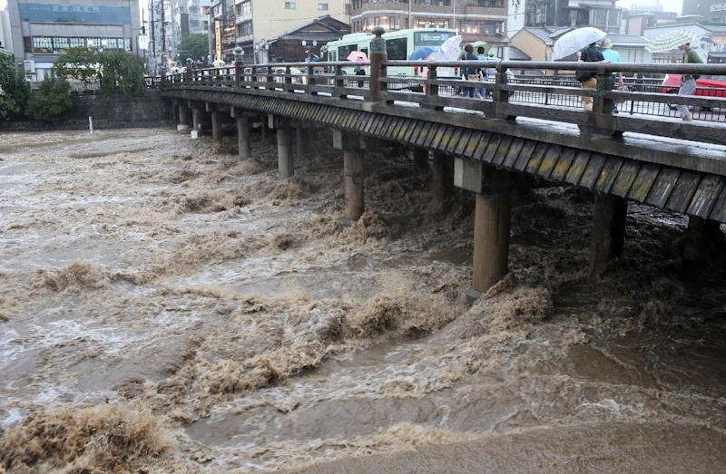 Photo taken on August 10, 2014 shows people crossing a wooden bridge over a flooded river in Kyoto, western Japan
