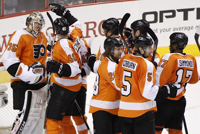 Philadelphia Flyers gather around goalie Steve Mason, left, as they celebrate their 2-1 win following the third period in Game 4 of an NHL hockey first-round playoff series against the New York Rangers, Friday, April 25, 2014, in Philadelphia. (AP Photo/Chris Szagola)