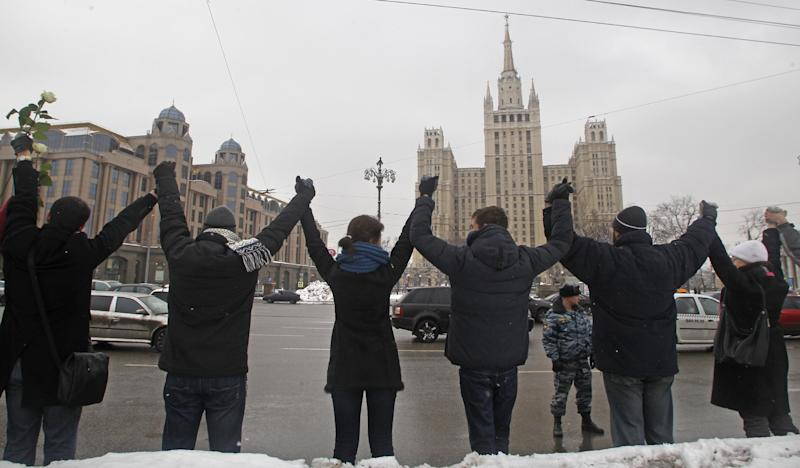 People stand along Garden Ring avenue holding hands during opposition protest in Moscow, Russia, Sunday, Feb. 26, 2012.  Thousands of people are holding hands to form a 16-kilometer (10-mile) human chain encircling central Moscow in the latest protest against Russian Prime Minister Vladimir Putin. Opposition activists estimated that they needed 34,000 people to complete the chain along the Garden Ring on Sunday and they appeared to have succeeded or come close. (AP Photo/Mikhail Metzel)