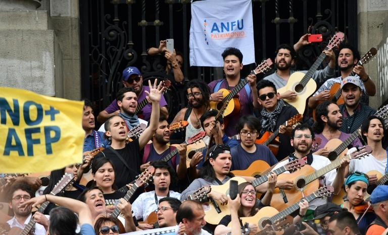 """Demonstrators play the guitar performing Chilean musician Victor Jara's """"The Right to Live in Peace"""" in Santiago, on October 25 (AFP Photo/Martin BERNETTI)"""