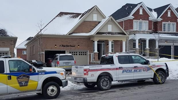 Emergency vehicles are seen parked near the home in Mount Albert where the Feb. 6 incident took place. Two people, including the 37-year-old suspect, died and three others survived knife attacks, including his two young sons.  (Michael Charles Cole/CBC - image credit)