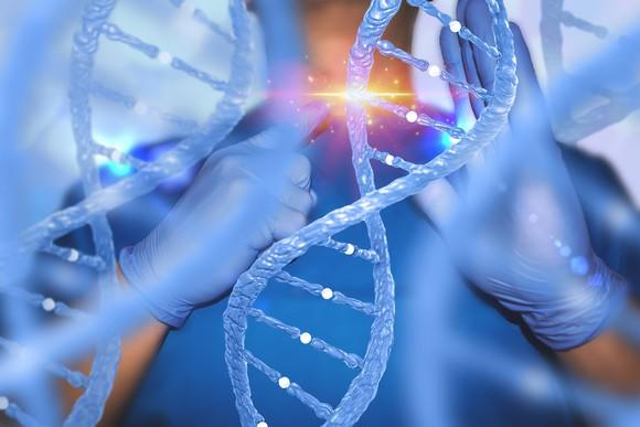 Enlarged image of DNA helixes in front of physician pointing to a section of the DNA with light appearing where he's pointing