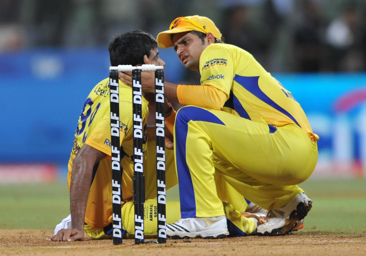 Chennai Super Kings fielder Suresh Raina (R) checks on team mate Ravichandran Ashwin after he was hit on the head by a ball during the IPL Twenty20 qualifier1 match between Chennai Super Kings and Royal Challengers Bangalore at Wankhede Stadium in Mumbai on May 24, 2011. AFP PHOTO / Sajjad HUSSAIN.