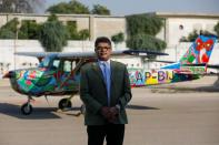Imran Aslam Khan, Chief Operating Officer of Sky Wings, poses with a Cessna aircraft painted with Pakistani truck art at Jinnah International Airport in Karachi