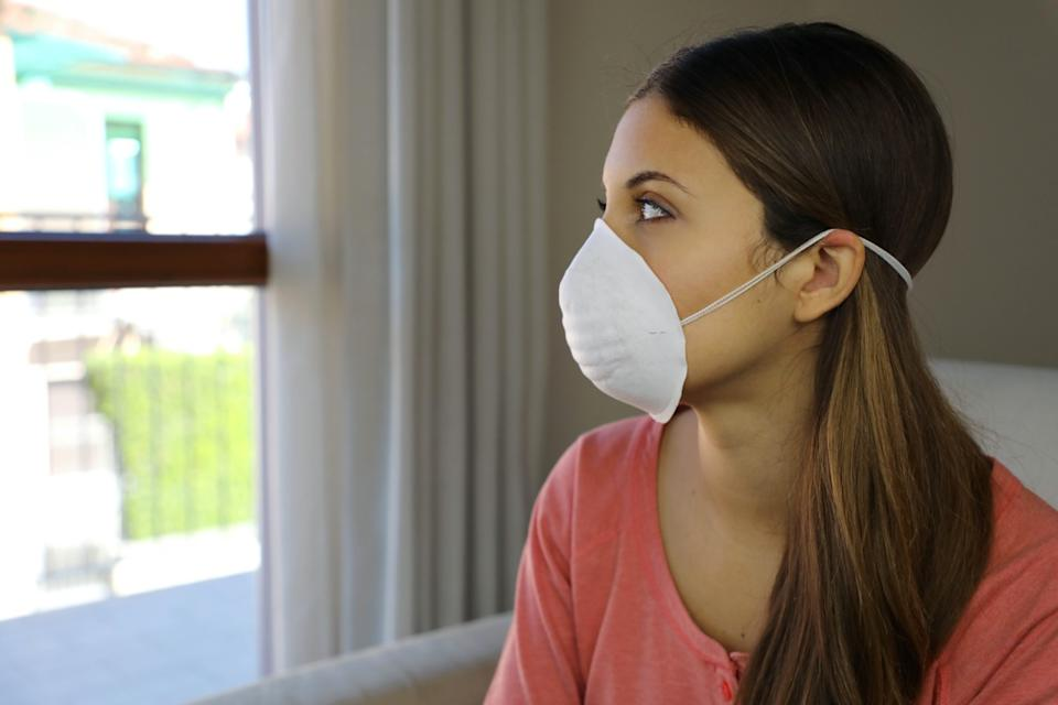 Woman at home wearing face mask.