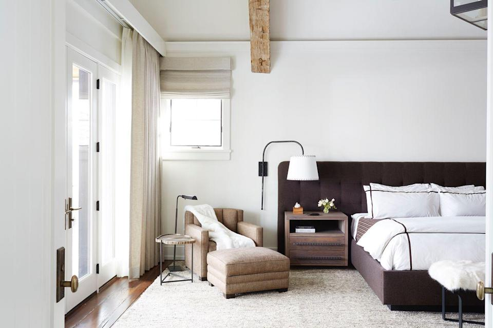 "<p>""The main bedroom in this Aspen home provides an open and airy respite with a tall vaulted ceiling lined with rustic wood beams,"" says Melanie Millner of <a href=""https://thedesignatelier.com/"" rel=""nofollow noopener"" target=""_blank"" data-ylk=""slk:The Design Atelier"" class=""link rapid-noclick-resp"">The Design Atelier</a> in Atlanta. ""We utilized the client's existing lantern chandelier and painted it black to help fill the expansive volume in the space and make the room feel warm and inviting. The headboard, nightstand and sconces were all custom designed. We had a local blacksmith build the sconce swivel arm and a local vendor made the white linen shade lined with chocolate lace trim. The sconce acts as a reading light at night and offers a soft glow in addition to the overhead lantern."" </p>"