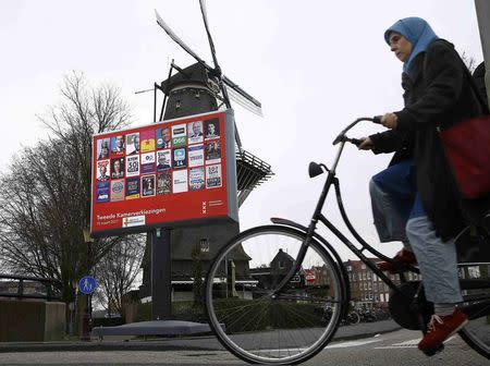 A woman cycles past an election poster billboard and a windmill the day before a general election in Amsterdam in the Netherlands