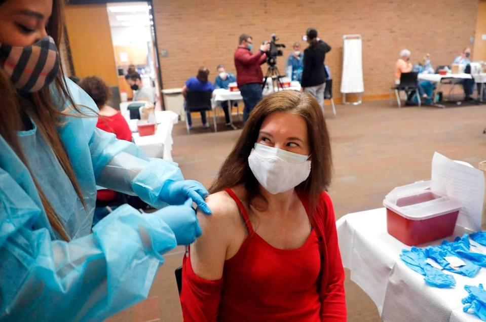 Natalie Macpherson, an English teacher at Sanderson High School, smiles after Crystal Truitt gave her a COVID-19 vaccine shot during a mass vaccine event at Wake County Commons Building in Raleigh, N.C., Wednesday, February 24, 2021. Wednesday was the first day preK-12 public, private and charter schools, as well as childcare workers, became eligible to begin getting shots.