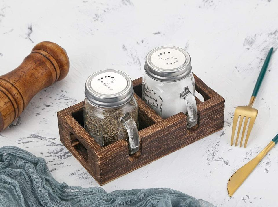 """Themini mason jars haveembossed details, and the wooden tray is handmade and hand-painted.<a href=""""https://amzn.to/37qqJ35"""" target=""""_blank"""" rel=""""noopener noreferrer"""">Find the set for $15 at Amazon</a>."""