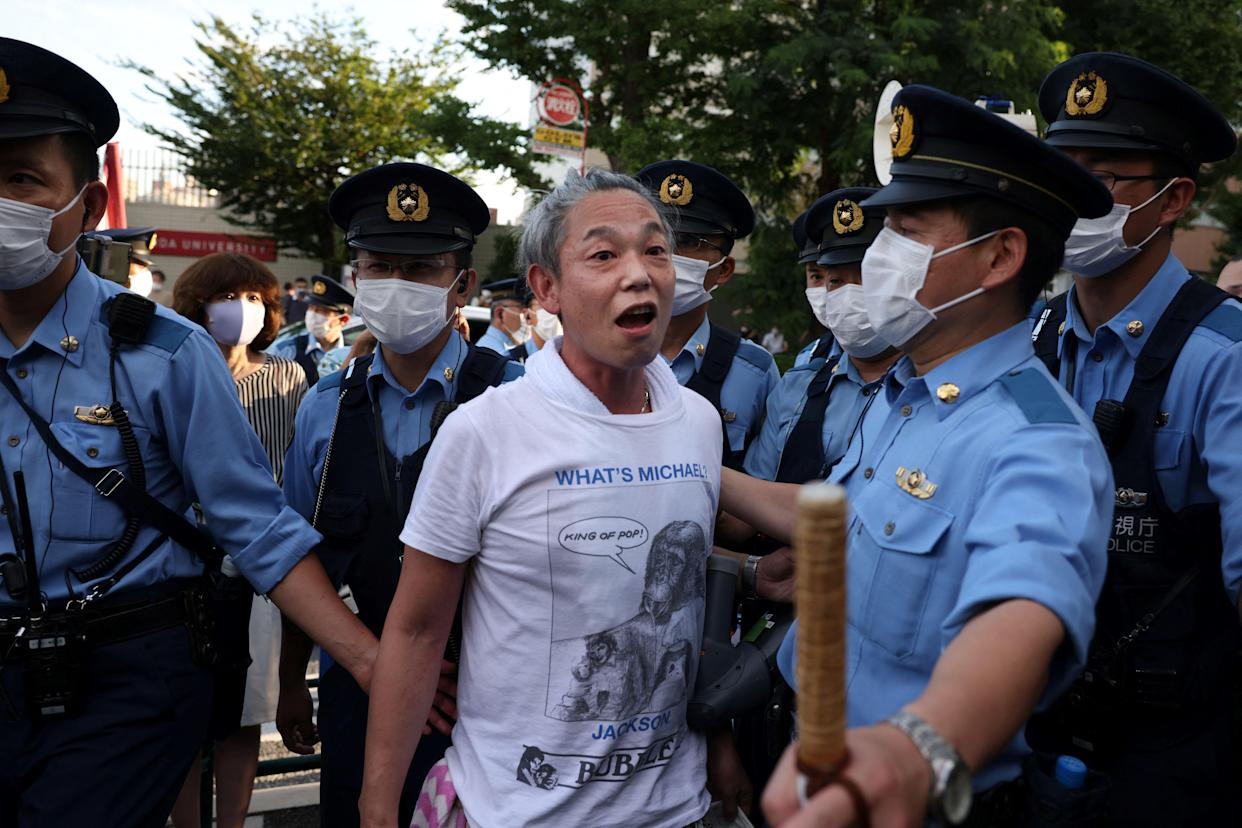 Police officers escort a protester protesting against the Tokyo 2020 Olympic Games after he got into an argument with a supporter of the Olympic Games near the Olympic Stadium in Tokyo on July 23, 2021, ahead of the opening ceremony of the 2020 Tokyo Olympic Games. (Photo by Yuki IWAMURA / AFP) (Photo by YUKI IWAMURA/AFP via Getty Images)