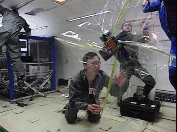 """This still from an experiment video shows a tiny cubesat satellite prototype after deploying a folded sail in weightlessness aboard NASA's """"Vomit Comet"""" research plane."""